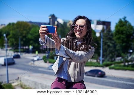 Mid shot of pretty woman taking selfie in front of city panorama