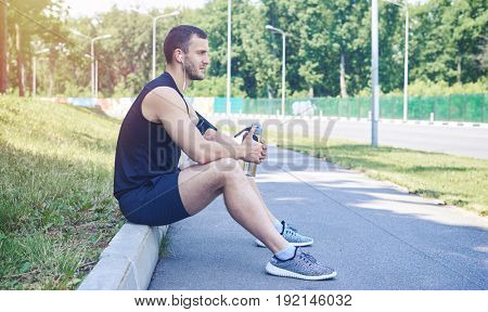 Mid shot a serious man wearing sport cloth, sitting on street curb, holding a bottle of water