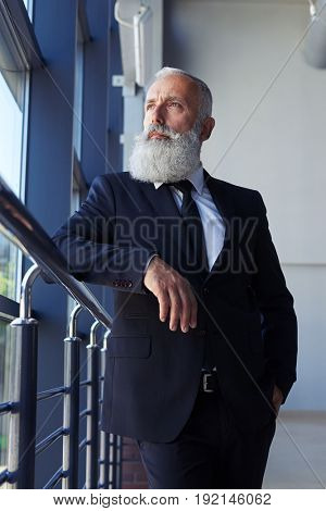 Vertical of pokerfaced man age of 50-60 looking out window while leaning on handrail