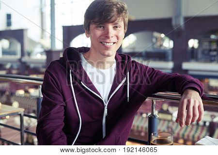 Mid shot of good-looking man sitting over cup of coffee in cafe