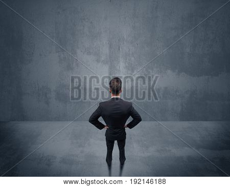 A young businessman with briefcase standing in blank empty space facing a grey urban wall, scratching his head concept.