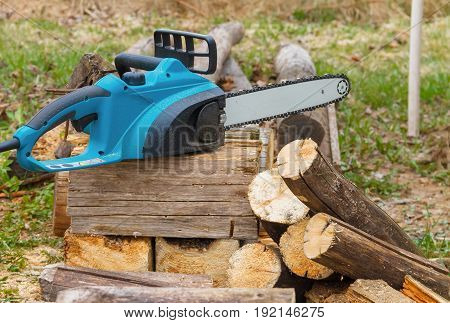 professional electric chainsaw on a pile of sawn logs