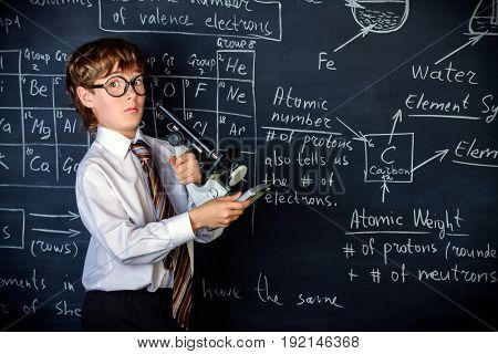 Serious schoolboy answering by a blackboard on a chemistry lesson. Educational concept.
