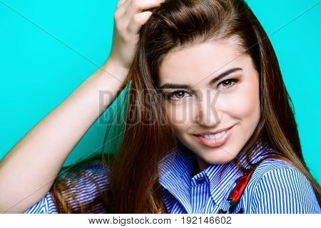 Portrait of a cheerful young woman with beautiful long hair over bright aquamarine background. Copy space. Beauty, haircare, skincare.