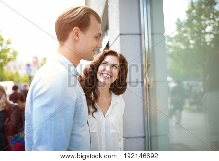 Young couple shopping together and watching a shop window in a city street
