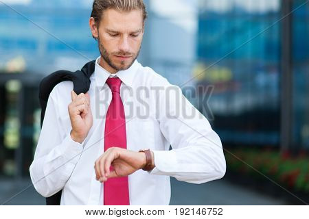Businessman looking at his watch in front of his office