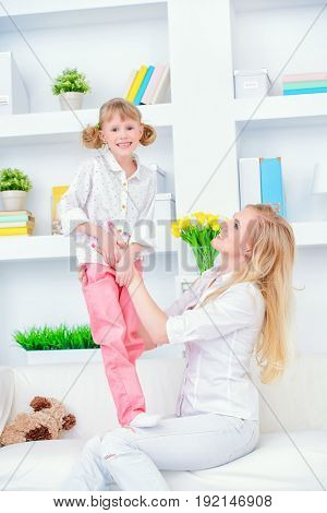 Happy family spending time together. Loving daughter plays with her dear mother.
