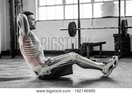 Digital composite of highlighted bones of exercising man at gym