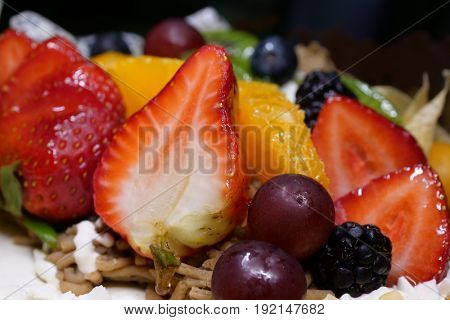 Fruit birthday cake on a black background