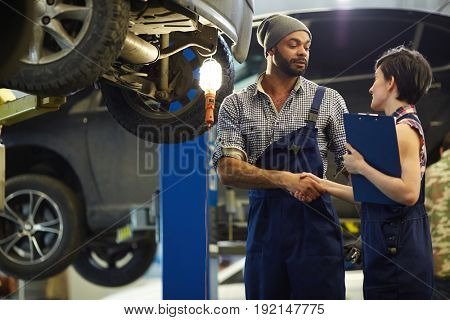 Two garage workers handshaking during work
