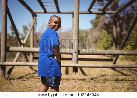 Portrait of happy boy standing with hands on hip during obstacle course in boot camp