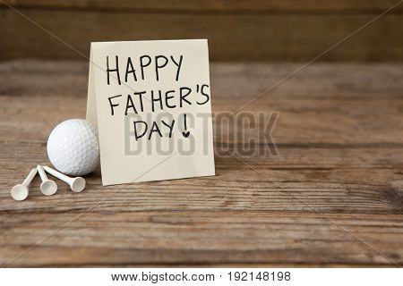 High angle view of fathers day greeting card by golf ball on wooden table