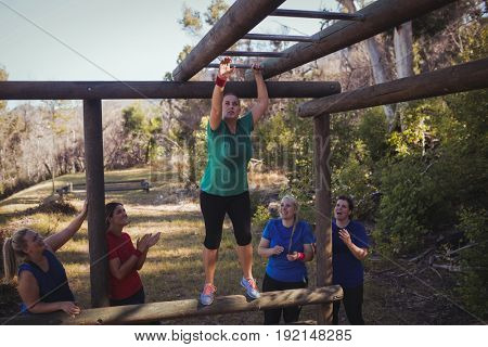 Woman being cheered bye her teammates to climb monkey bars during obstacle course training in the boot camp