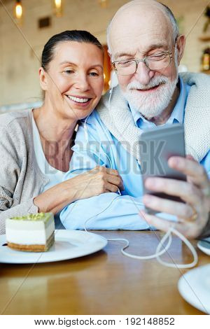 Seniors with smartphone watching video in the net