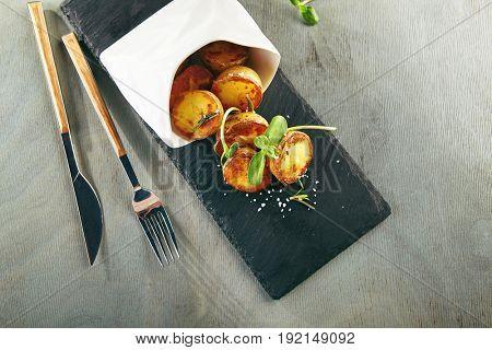 Restaurant Food - Potato Fried. Potato Wedge Garnish on Black Slate Plate. Garnish Restaurant Menu