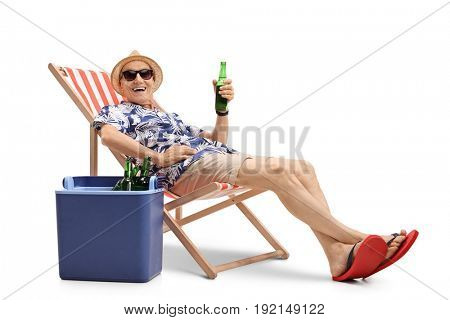 Elderly tourist with a bottle of beer sitting in a deck chair next to a cooling box and looking at the camera isolated on white background