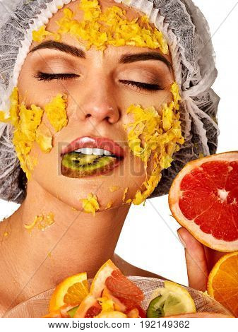 Facial mask from fresh fruits for woman. Girl in medical hat with mango pulp, grapefruit and kiwi as ingradients for face care smooth skin on isolated. Girl eating piece of kiwi. Facial rejuvenation.