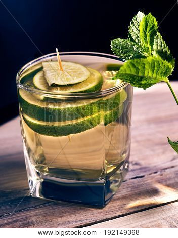 Non alcohol drink. On wooden boards is glass with green transparent drink. Soft drink with lime and mint leaf on black background. Country life.