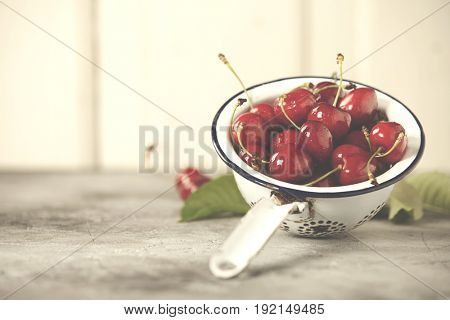 White colander filled with fresh cherries over a rustic background