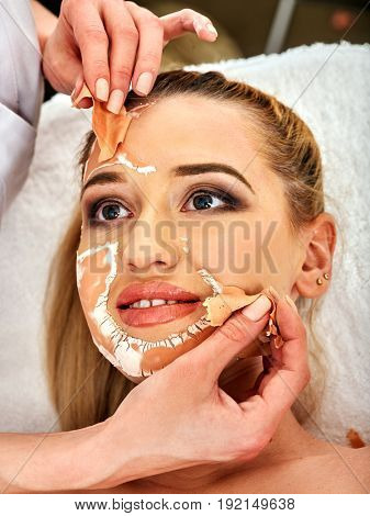 Collagen face mask. Facial skin treatment. Woman receiving cosmetic procedure in beauty salon. Bottle with moisturizing cream on background. Cropped shot of removing wrinkles. Mask against black dots.