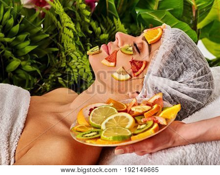 Facial mask from fresh fruits for woman. Beautician apply mango pulp, grapefruit and kiwi. Girl in medical hat lying on spa bed for skin care ethnoscience procedure in salon.