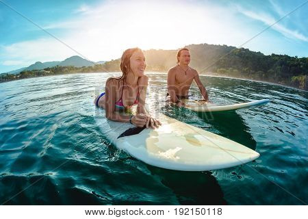 Couple of surfers waits the waves in the ocean