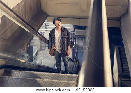 Asian man on escalator going up
