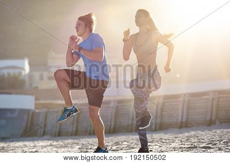Fit active lifestyle, couple working out on beach with sun flare