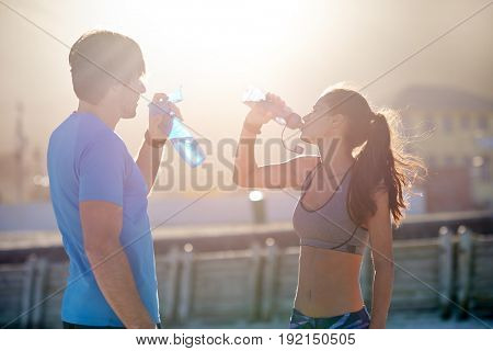 Active fitness couple hydrating drinking water in between their exercises  after their run