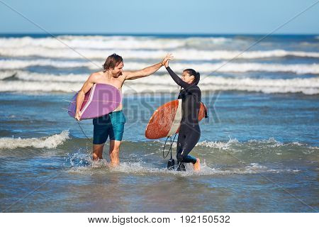 FIt healthy couple high five after surfing, walking out of ocean water surf waves summer hobby active lifestyle