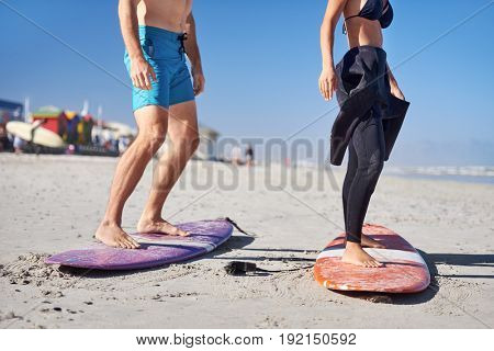anonymous couple learning how to surf, legs  standing up on surfboards on the beach
