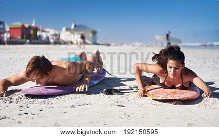 couple learning how to surf, practicing paddling and standing up on surfboards on the beach