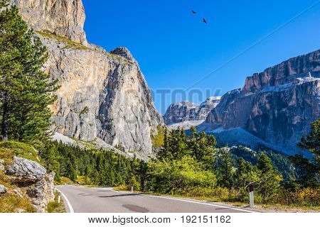 Picturesque road through the Sella Pass, Dolomites. Autumn in the Tirol. The concept of ecological and extreme tourism. Impressive ridge of dolomite rocks