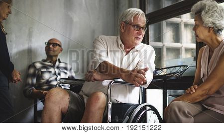 Senior man on a wheelchair talking with his friend