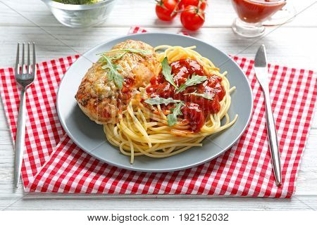 Delicious pasta with chicken parmesan and sauce on plate