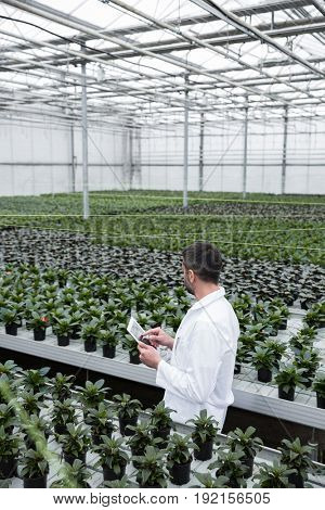 Picture of young concentrated man standing in greenhouse near plants holding tablet computer. Looking aside.