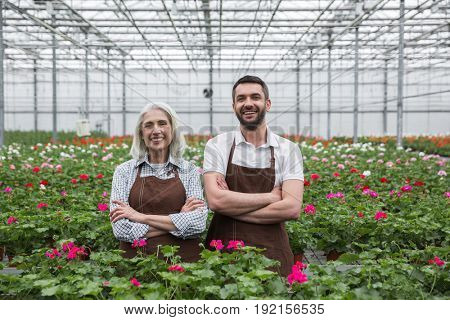 Image of young cheerful man standing in greenhouse near mature woman and plants. Looking aside.
