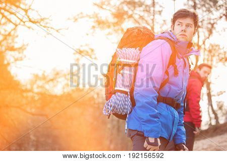 Male hiker looking away with friend in background at forest