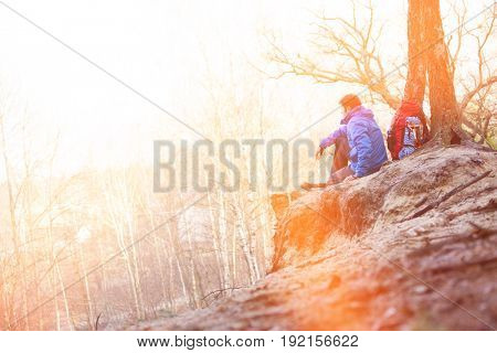Side view of male hiker sitting on edge of cliff in forest