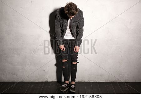 Image of serious hipster man looking aside over gray background