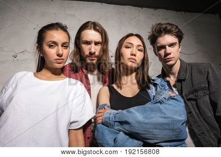 Image of young serious hipsters friends standing over gray background looking camera.