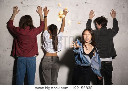 Image of young angry hipsters loving couples standing over gray background. Woman scatter bread Looking camera.