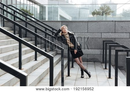 Fashion portrait of serious young blonde lady outdoors. Looking aside holding cigarette.