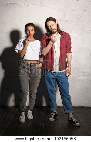 Image of young hipster man standing over gray background with cigarette near girlfriend eating candy.