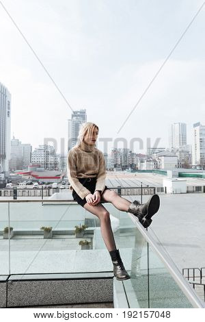 Fashion portrait of concentrated young blonde lady outdoors. Looking aside.