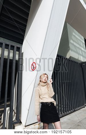 Fashion portrait of serious young blonde lady with cigarette outdoors. Looking at camera.