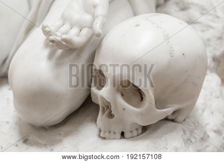 Stone statue of human skull with hand.