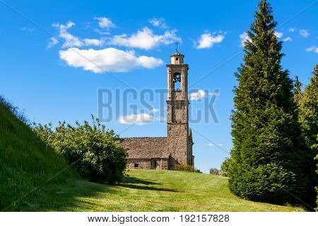 Old stone parish church under blue sky in small town of Prunetto, Italy.