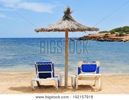 detail of a relaxing area in a beach in Ibiza, Spain, with two comfortable sunloungers and a rustic umbrella made of natural fibers