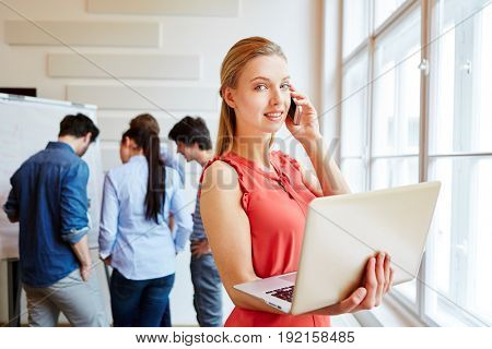 Businesswoman during meeting with her start-up team and her laptop calling on the phone